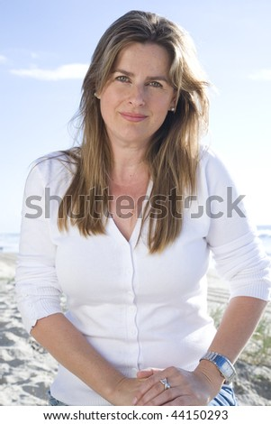 Woman sitting on the beach on a sunny day - stock photo