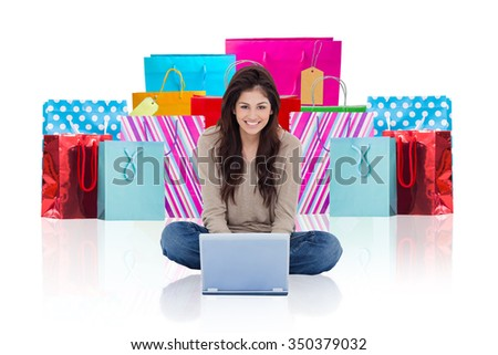 Woman sitting on the bed with the laptop in front of her and smiling against white background with vignette - stock photo