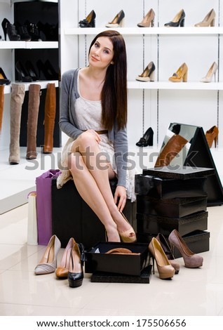 Woman sitting on the chair and trying on shoes in the shop can't decide what to buy - stock photo