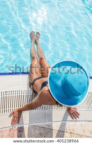 Woman sitting  on the edge of swimming pool. - stock photo