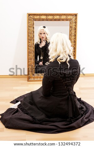 Woman sitting on the floor in front of the mirror