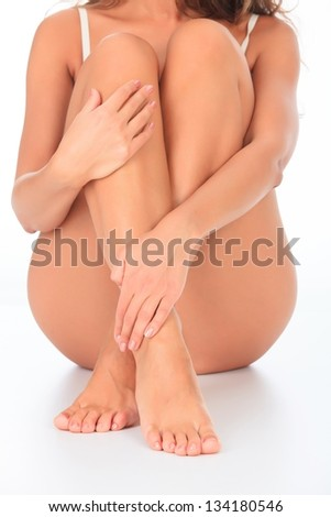Woman sitting on the floor touches leg by hand - stock photo