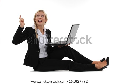 woman sitting on the floor with her laptop and having a great idea - stock photo