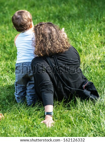 woman sitting on the grass pointing something to her very young son standing next to her - stock photo