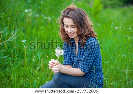 woman sitting on the grass with dandelion.