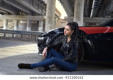 woman sitting on the pavement next to the car