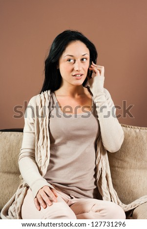 Woman sitting on the sofa and talking on the phone,Young woman using mobile phone - stock photo
