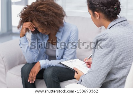 Woman sitting on therapists couch looking down with therapist taking notes - stock photo