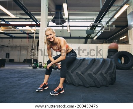 Woman sitting on tire and smiling at camera at gym. Crossfit female athlete taking rest after working out. - stock photo