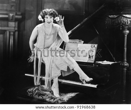 Woman sitting on top of a grand piano