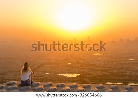 Woman sitting on top of skyscraper overlooking the city at sunrise - stock photo