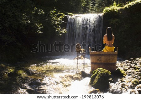 Woman sitting on tub, outdoor - stock photo
