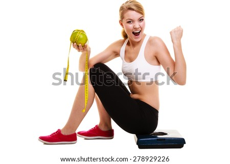 Woman sitting on weighing scale, holding grapefruit and measurement tape clenching her fist. Successful diet dieting slimming. Healthy lifestyle and body care concept. - stock photo