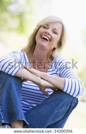 Woman sitting outdoors laughing - stock photo