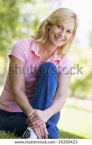 Woman sitting outdoors smiling - stock photo