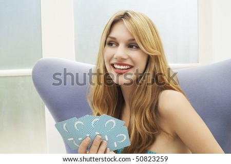 Woman sitting Playing Cards, portrait - stock photo