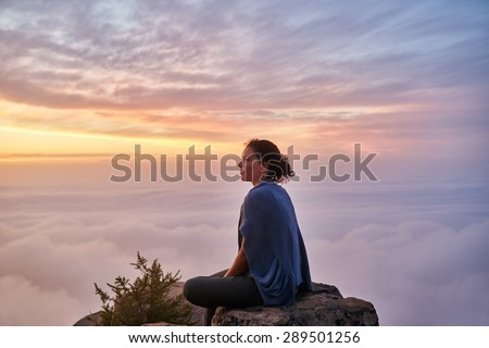 Woman sitting quietly on mountain top surrounded by serene clouds in pastel colours with early morning mist and clouds below her - stock photo