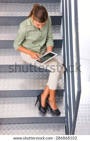 Woman sitting staircase using digital tablet - stock photo
