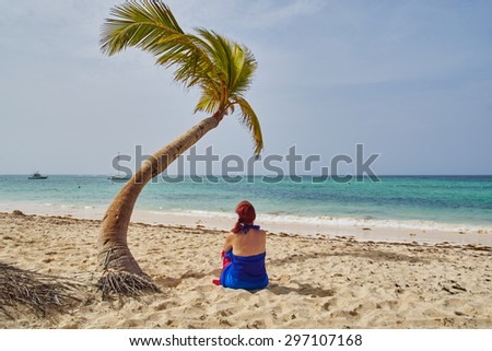 woman sitting under coconut tree stock photo royalty free