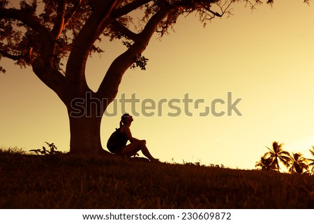 Woman sitting under the tree and watching a sunset - stock photo