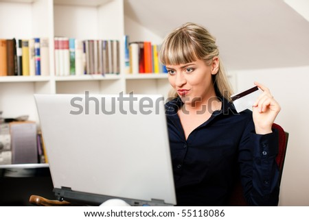 Woman sitting with a laptop in her home living room in front of a book shelf shopping or doing banking transactions online in the Internet, emphasized by her holding a credit card - stock photo