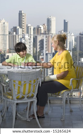 Woman sitting with boy on balcony. Woman mentoring boy. Woman wearing cast. Vertically framed photo. - stock photo