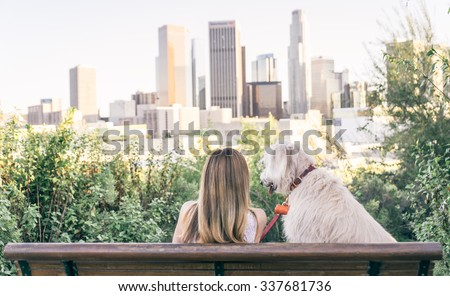 Woman sitting with her dog and enjoying the skyline view  - stock photo