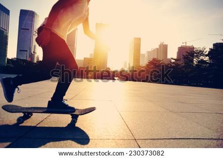 woman skateboarder legs skateboarding at sunrise city  - stock photo