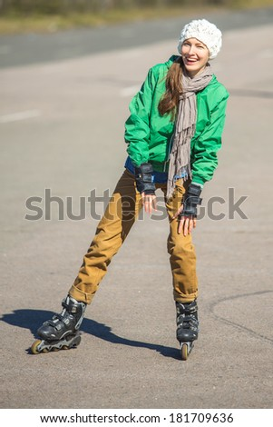 woman skating with rollerblades in a park happy smiling - stock photo
