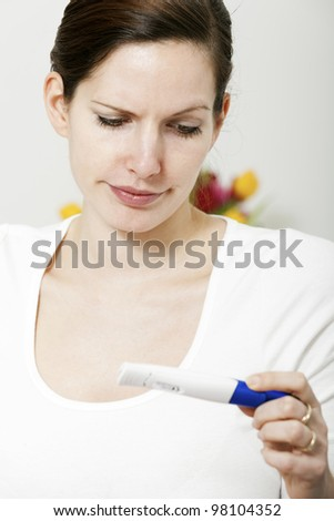 Woman skeptical over pregnancy test - stock photo