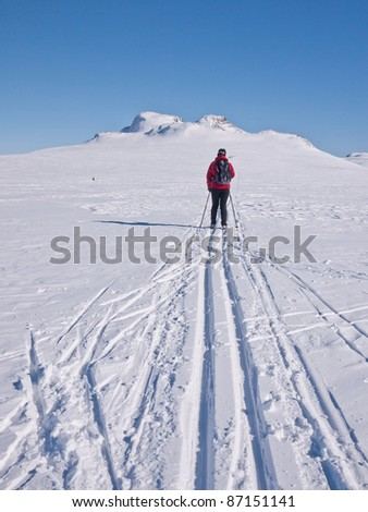 Woman skiing alone in a groomed single ski track heading towards some twin mountain summits in the norwegian mountains at easter - stock photo