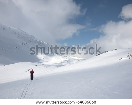 Woman skiing alone in a valley with various lighting conditions and mountain summits and clouds in the background in the norwegian mountains - stock photo