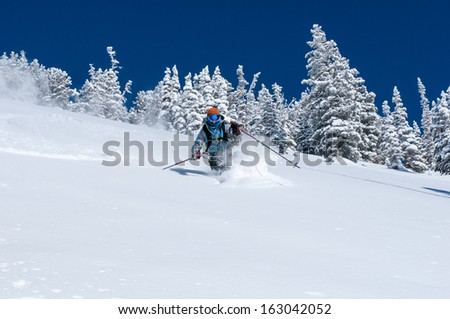 Woman skiing deep powder near Alta Ski Area Wasatch Mountains Utah - stock photo