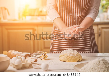 Woman slap his hands above dough closeup. Baker finishing his bakery, shake flour from his hands, free space for text.