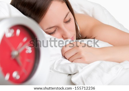 Woman sleeping in a bed with an alarm clock next to her - stock photo