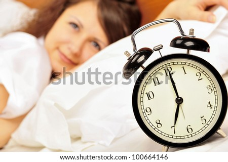 Woman sleeping in bed and alarm-clock (focus on alarm clock)