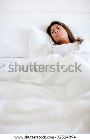 Woman sleeping in bed looking very comfortable - stock photo