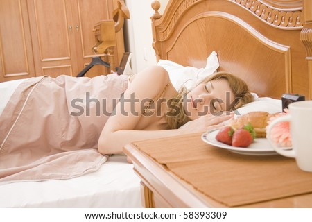 Woman sleeping in bedroom, with the breakfast at nightstand . - stock photo