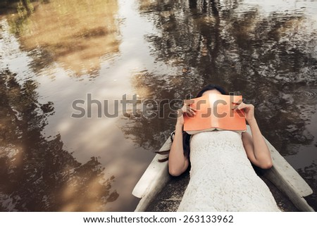 Woman sleeping in boat with her face covered by a book