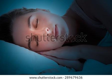 Woman sleeping in the dark - stock photo