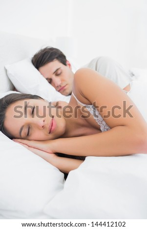 Woman sleeping next to her partner in bed - stock photo
