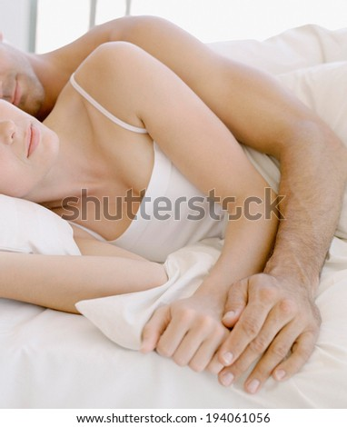 Woman sleeping peacefully on her husbands chest in bed - stock photo