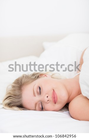 Woman sleeping with a smile in her bed - stock photo