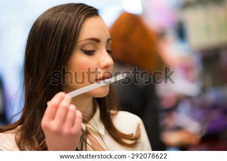 Woman smelling a perfume tester in a shop - stock photo