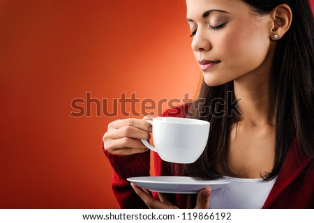 Woman smelling hot drink and holding mug isolated in studio - stock photo