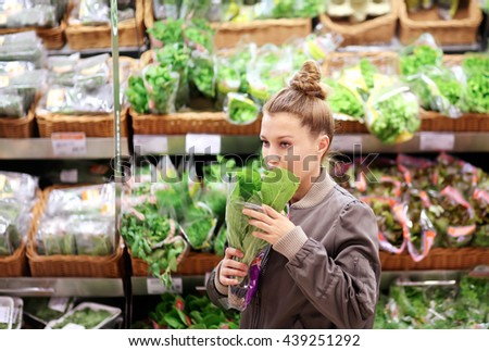 Woman smelling lettuce in the supermarket - stock photo