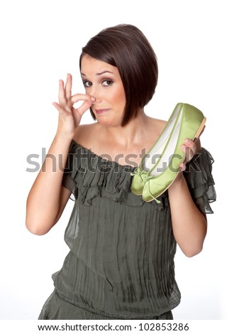 woman smells bad odor on her shoes - stock photo