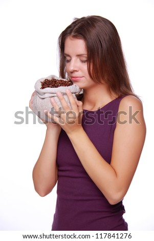 Woman smells  coffee beans isolated on white/Lovely girl with sack of coffee
