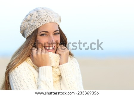 Woman smile with a perfect white teeth in winter with the beach in the background - stock photo