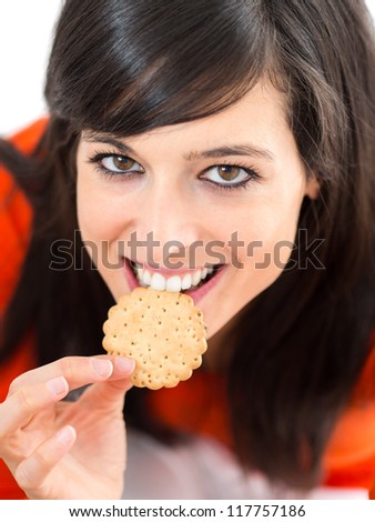 Woman smiling and biting a crunchy biscuits. Eating with funny looking face and eyes. - stock photo